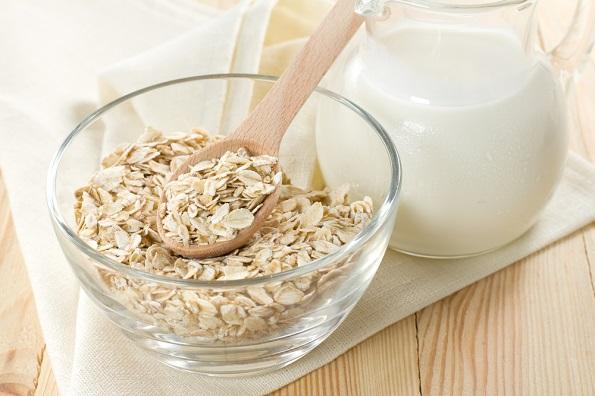 Oat flaks on a glass boel and jug of milk